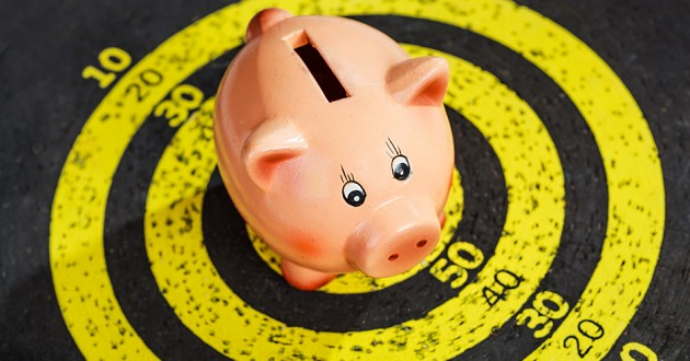 A piggy bank in the center of a dartboard.