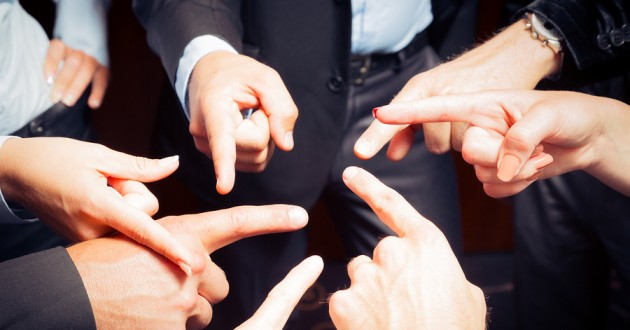 People in business attire pointing fingers at each other.