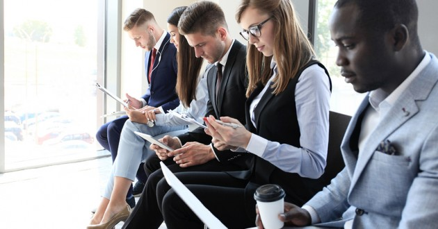 Professionals sitting in a row wearing business attire.