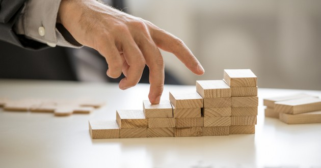 A hand assembling wooden blocks in a staircase formation on a table.