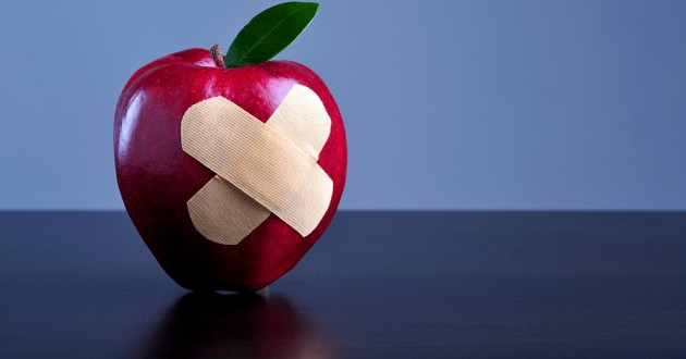 Two adhesive bandages criss-crossed on an apple.