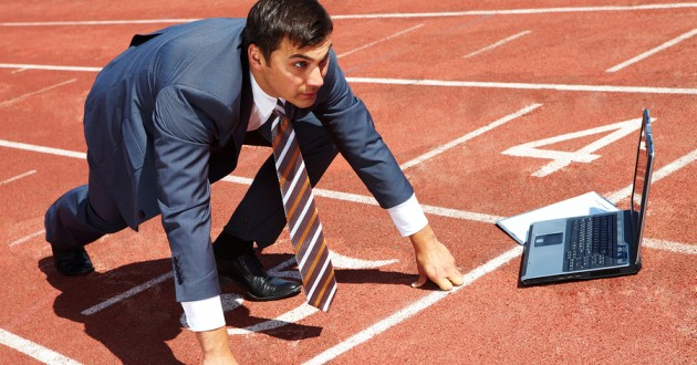 A man in business attire positioned to begin a race on a track next to a laptop computer.
