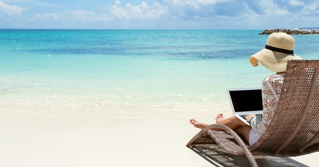 A woman typing on a laptop while lounging on a beach.