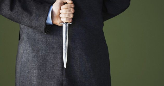 A close up of a businessman holding a dagger behind his back.