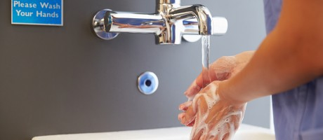 A health care worker washing her hands in a sink.