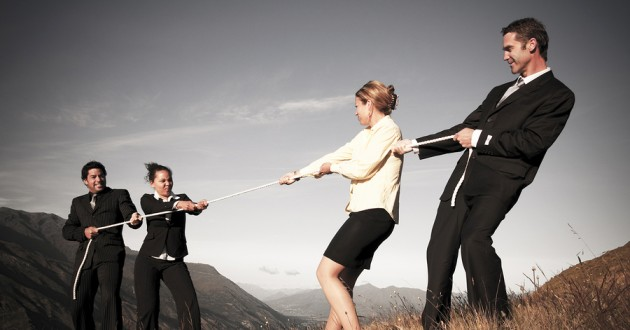 People in business attire competing in a game of tug of war.