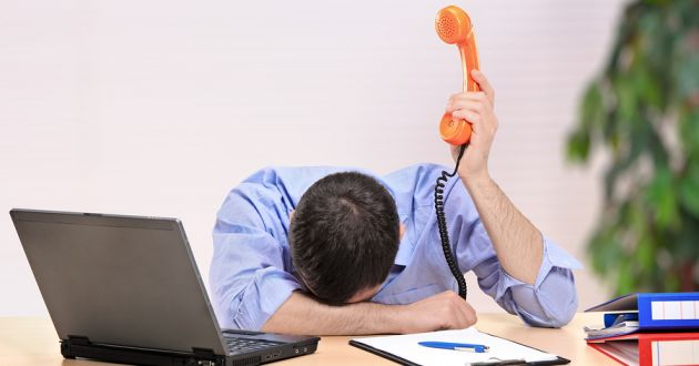 An exasperated businessman holding up a phone with his head on an office desk.
