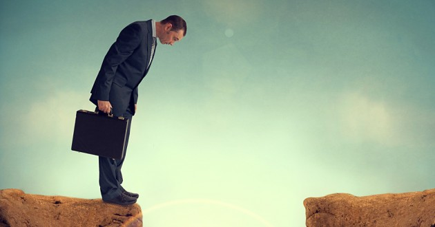 A man holding a briefcase and looking down through a gap between two cliffs.