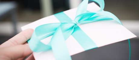 A hand holding a gift envelope tied with a blue ribbon.