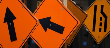 Several traffic signs pointing in different directions.