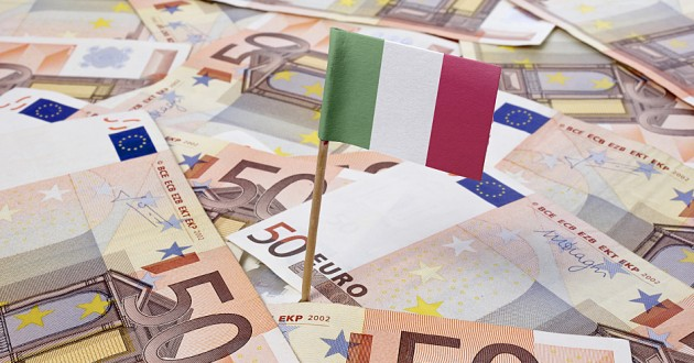 An Italian flag driven into a surface covered with European banknotes.