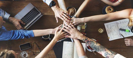 Colleagues joining hands at the center of a table as a gesture of collaboration.