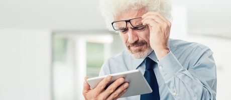 A man in business attire lifting his glasses to look at data on a smart tablet.