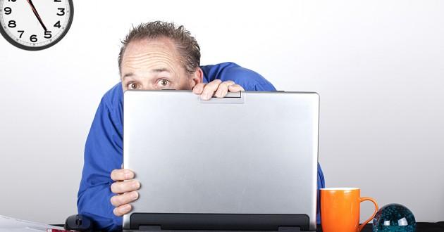 A man hiding behind a laptop computer.