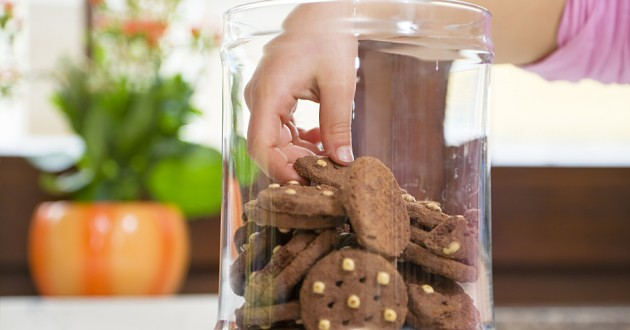 A hand taking a cookie from a glass jar.