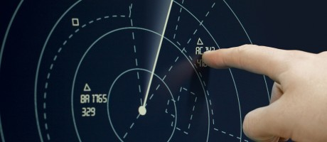 A hand pointing to a blip on a sonar display.