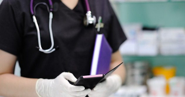 A health care professional using a smartphone in a medical facility.