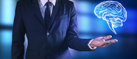 A businessman gesturing toward a floating illustration of the human brain.