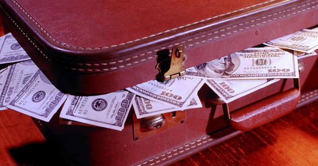 A leather suitcase with money overflowing out of its sides.