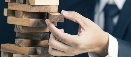 Businessman removing a risky Jenga piece from a tower.
