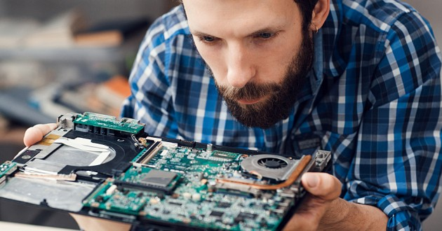 Young man studying computer motherboard, close-up.