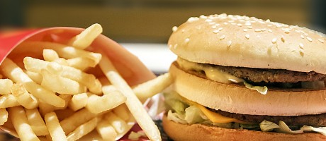 A double-stacked burger placed next to french fries.