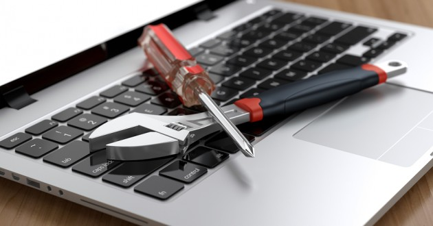 A wrench and a screwdriver on a computer keyboard.