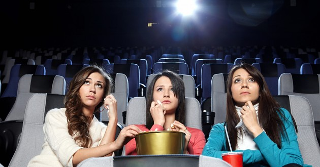 Three women crying and eating popcorn at a movie theater.