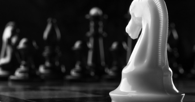 A white knight chess piece in the foreground with black pieces in the background.