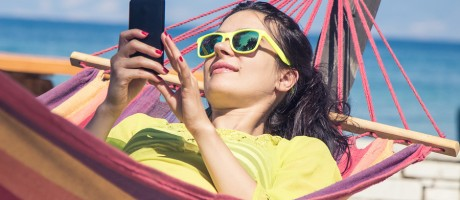 A woman using a smartphone while lounging in a hammock on the beach.