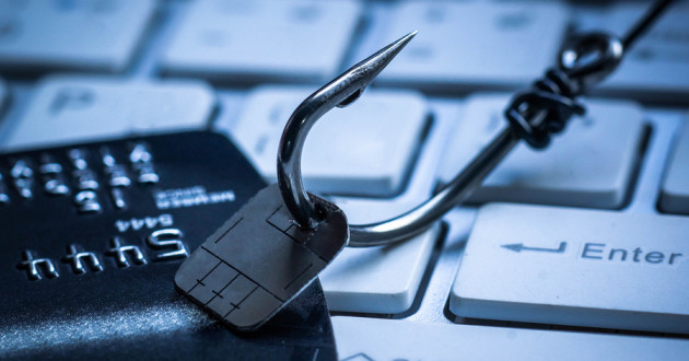 A fishing hook grabbing a credit card chip with a keyboard in the background.