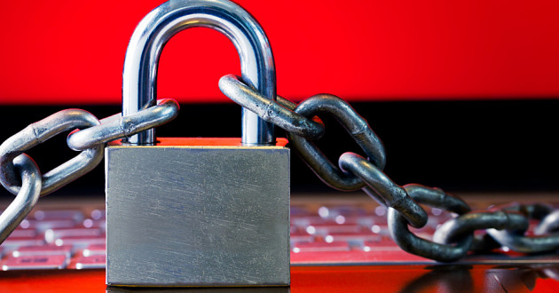 A large padlock and chain on a laptop keyboard with a bright red screen in the background.