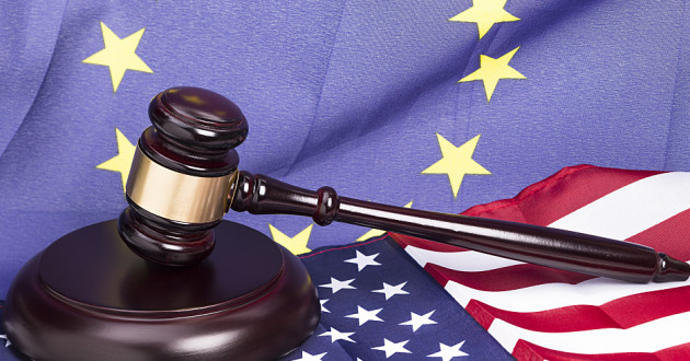 A wooden gavel resting on a U.S. flag with an EU flag in the background.