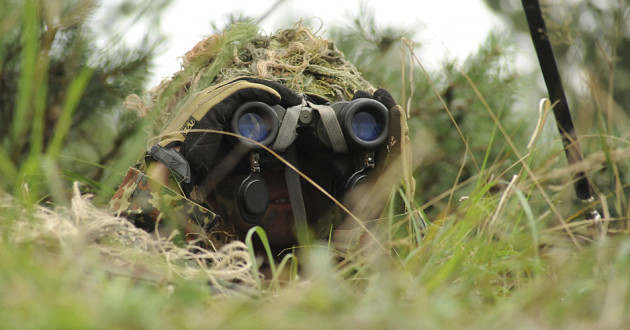 A solider using binoculars to spy on an enemy.
