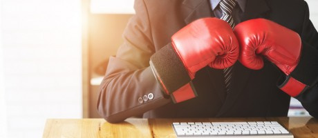 Man in business attire at his desk wearing boxing gloves.