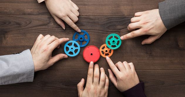 Five hands manipulating colorful gears on a wooden table.
