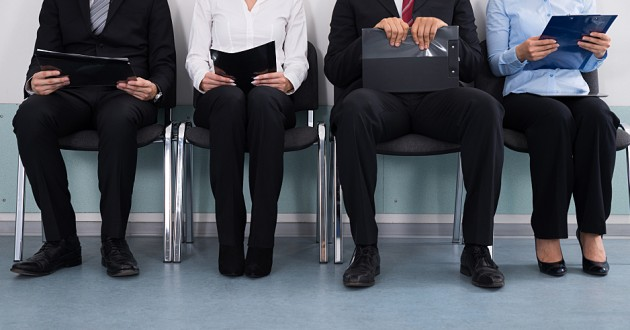 Four professionals waiting for a job interview.