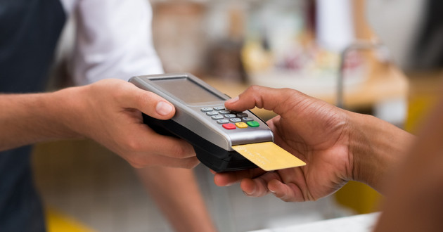 A retailer and customer conducting a transaction at a point-of-sale terminal.