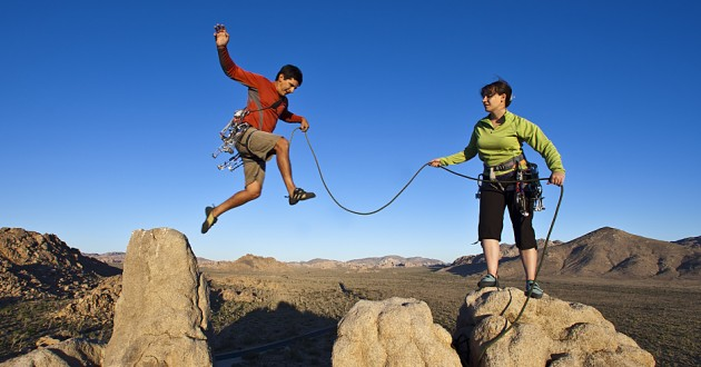Two members of a climbing team traversing between rocks.