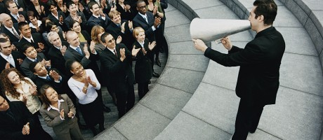 A business leader delivering a message to a large group of employees through a megaphone.
