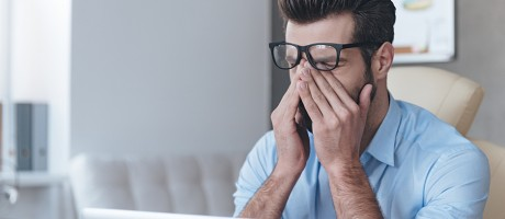 A man rubbing his eyes in front of a laptop.