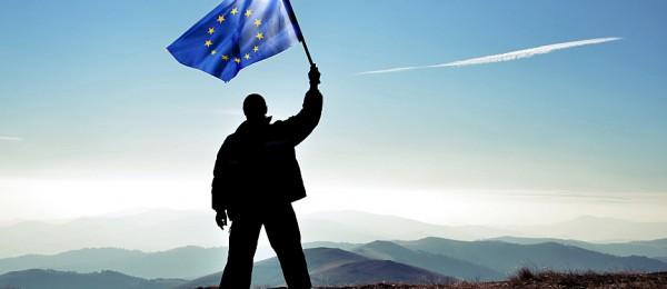 A man waving a European Union flag in a remote area.