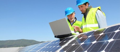 Two utilities workers using a laptop on top of a solar energy panel.