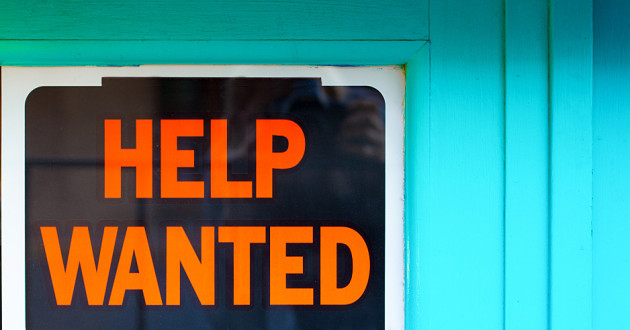 "A ""help wanted"" sign posted on a window with bright blue trim."