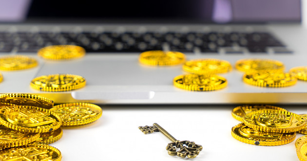 Gold-colored coins and a key on a laptop keyboard.