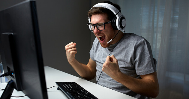 A young man wearing a headset and celebrating while looking at a desktop computer screen.