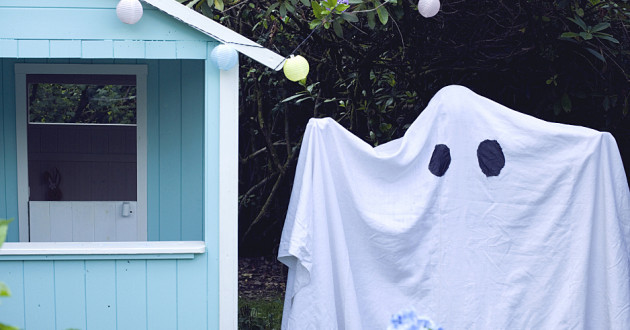 A person wearing a ghost costume next to a small blue hut.