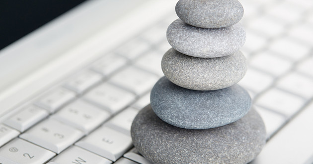 Five stones balancing on a laptop keyboard.
