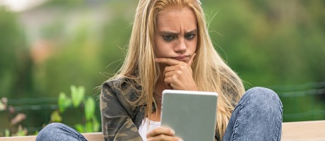 A woman reading from a digital tablet with an expression of skepticism.
