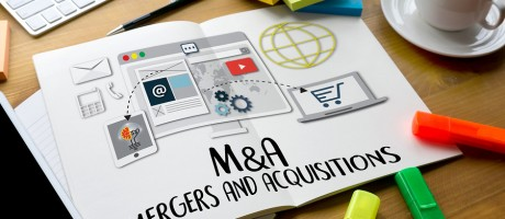 "A mockup of a website sitting on a desk with the words ""Mergers and Acquisitions"" written out on the page."
